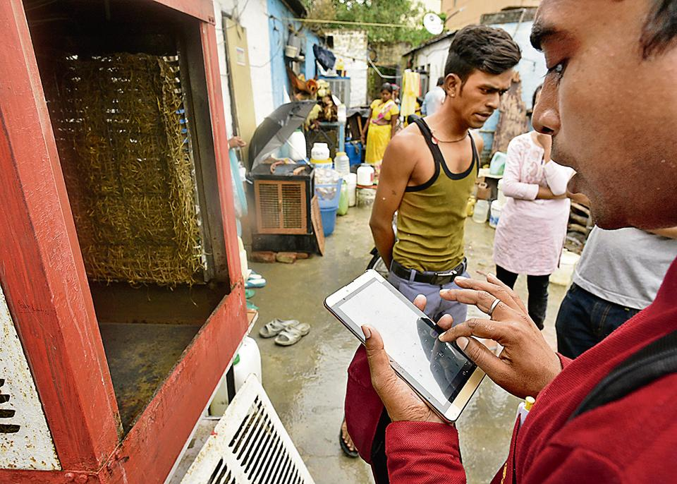 Workers of SDMC's malaria department use a mobile tablet to note down information at Kishangarh village near Vasant Kunj in New Delhi.
