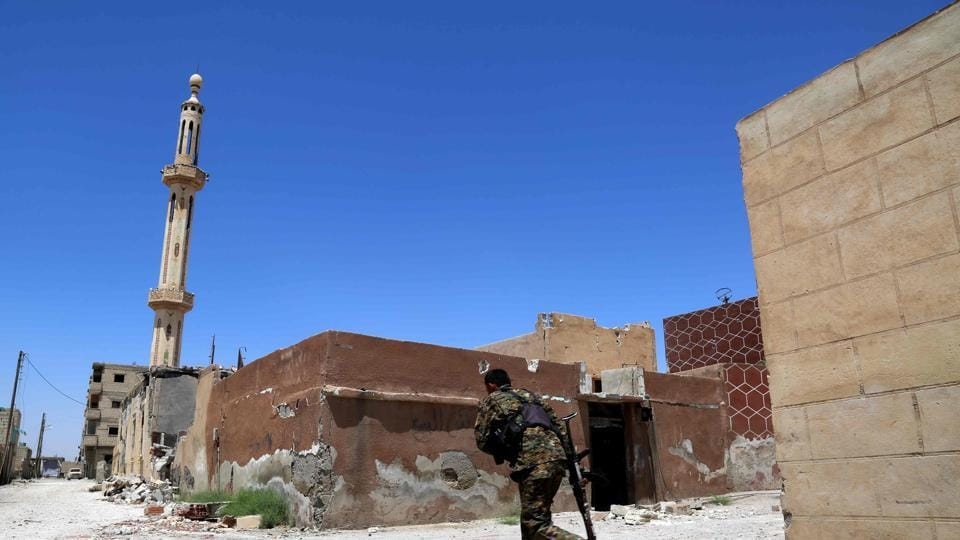 A member of the Syrian Democratic Forces (SDF), made up of an alliance of Kurdish and Arab fighters, crosses a street on June 27, 2017 in the suburb of Dariya on the western city limits of Raqa after the area was seized by SDF from the jihadists.