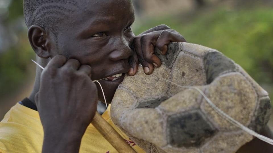 A South Sudanese refugee boy repairs an old soccer ball with thread, in the Bidi Bidi refugee settlement in northern Uganda. In a bid to keep young people busy, the International Rescue Committee and other aid groups are hosting inter-village competitions meant to forge unity among the refugees, most of whom recently fled to Uganda to escape civil war. At Bidi Bidi, the world's largest refugee settlement, youth from South Sudan are drawn to soccer, a rare source of entertainment in an otherwise dreary existence.  (Ben Curtis / AP)