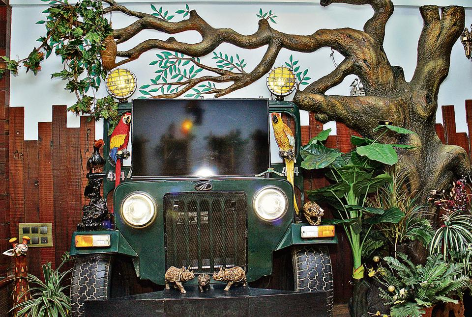 For a jungle themed home at the Pandits', a part of a jeep has been stuck under a tree on which they place their television.