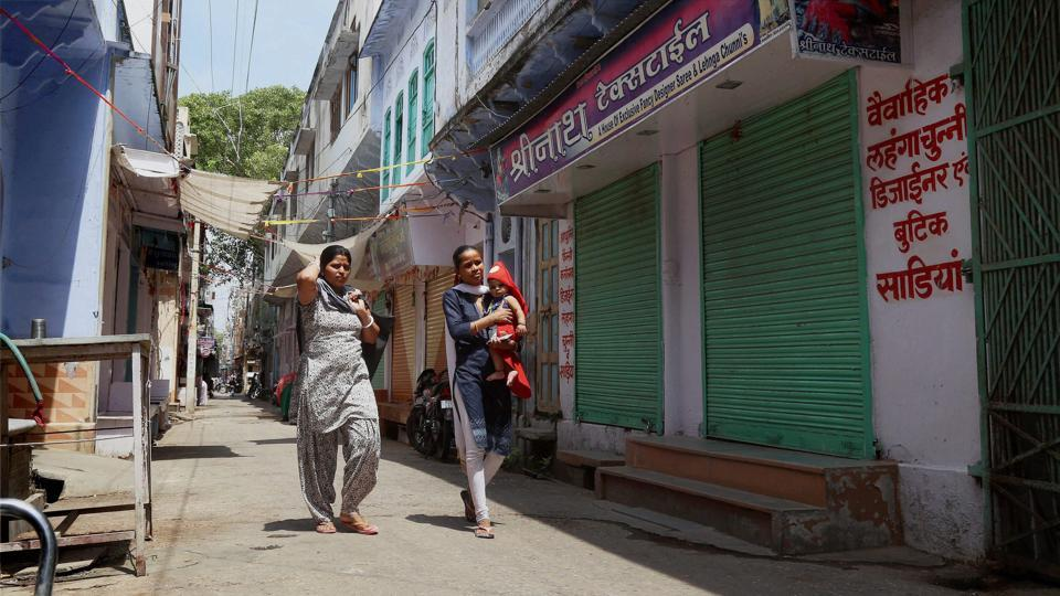 Women walk past textile shops that were closed in protest against some provisions of the Goods and Services Tax at Beawar on Thursday.