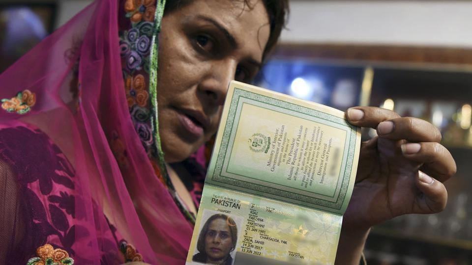 Pakistani transgender Farzana Riaz displays her newly-obtained passport in Peshawar on June 28, 2017.