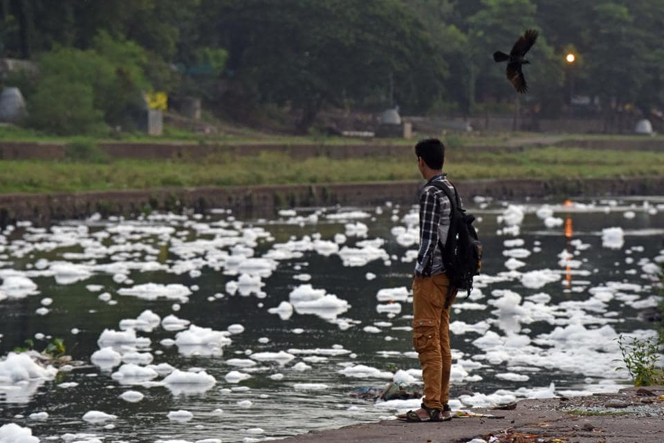 A boy looks at foam formation in Mutha River in Pune, India, on Saturday
