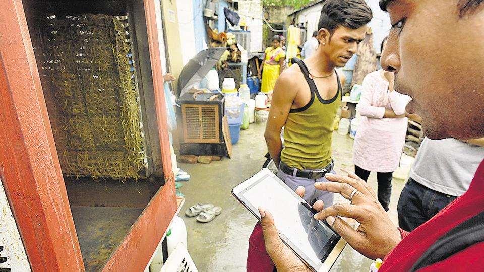 Workers from SDMC's malaria department use a tablet to note down information at Kishangarh village near Vasant Kunj in New Delhi on Friday.