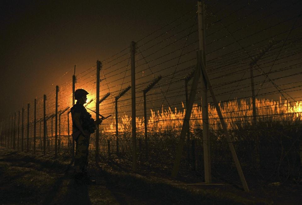 BSF soldier standing guard during a night patrol near the fence at the India-Pakistan International Border at the outpost of Akhnoor sector, about 40 km from Jammu.