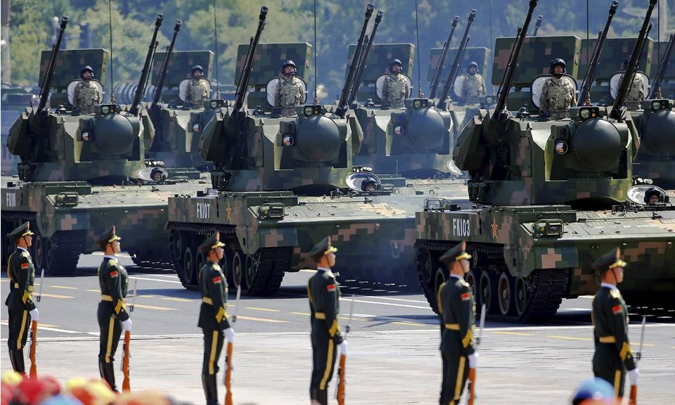 People's Liberation Army soldiers and armoured vehicles equipped with anti-aircraft artillery at Tiananmen Square during a military parade.
