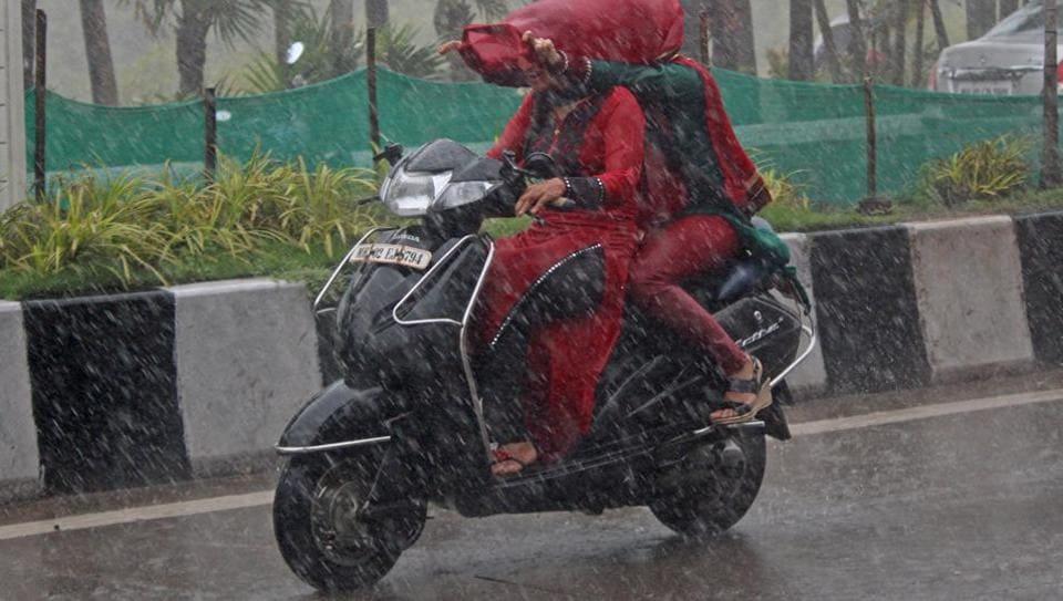Women drive through heavy rainfall in Carter Road, Bandra, on Wednesday.