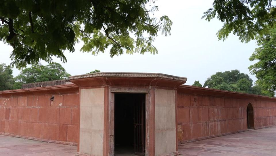 Najaf Khan's Tomb in central Delhi comprises a stone platform surrounded by trimmed lawns and centuries-old stone walls.
