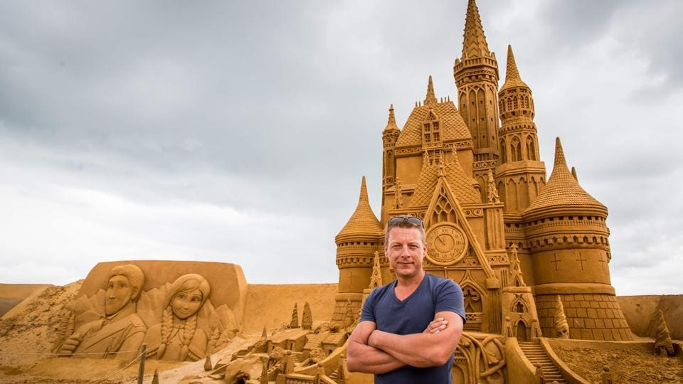 Alexander Deman, the organiser of Disney Sand Magic, poses in front of sand sculptures representing characters and scenes of Disney movies during an exhibition Disney Sand Magic in Ostende. (Aurore Belot  / AFP)