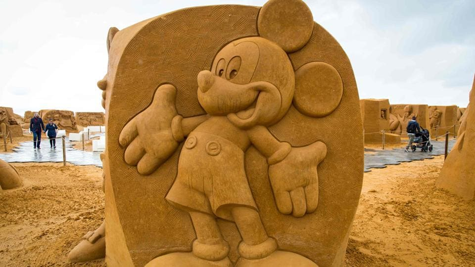 People walk past sand sculptures of Mickey mouse  during an exhibition Disney Sand Magic. (Aurore Belot  / AFP)