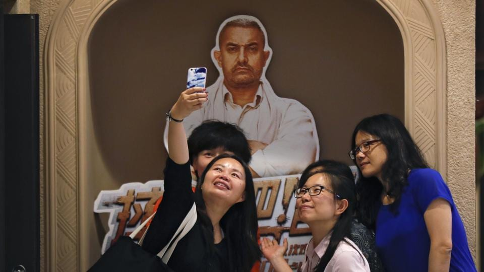 Women take a selfie with a poster of Bollywood blockbuster Dangal on display at a cinema in Beijing
