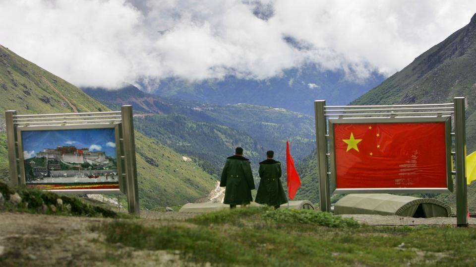 Chinese army officers oversee preparations as they stand on the Chinese side of the international border at Nathula Pass, in Sikkim, Wednesday, July 5, 2006.