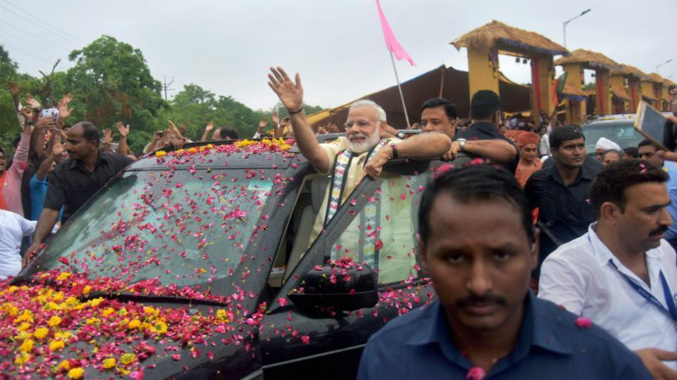 Prime Minister Narendra Modi waves at supporters during a road show in Rajkot, Gujarat, on Thursday.