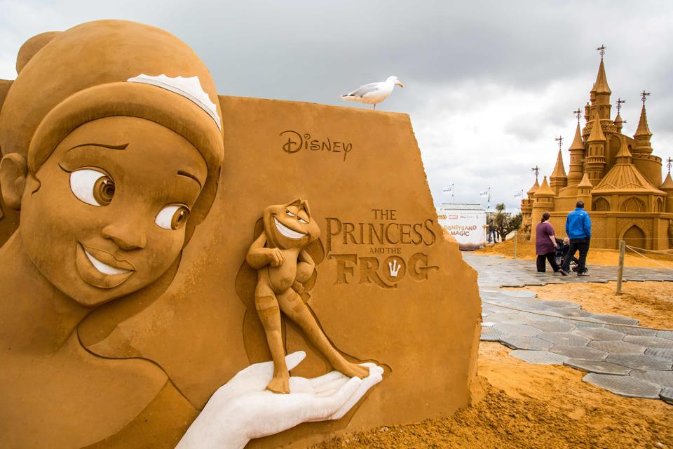 People stand next to sand sculptures representing characters and scenes of Disney movies during an exhibition Disney Sand Magic in Ostende. Disneyland Paris is celebrating its 25th anniversary with an array of sand sculptures on the beach of Ostend in Belgium. This year's artwork was created by over 40 artists from around the world. (Aurore Belot  / AFP)