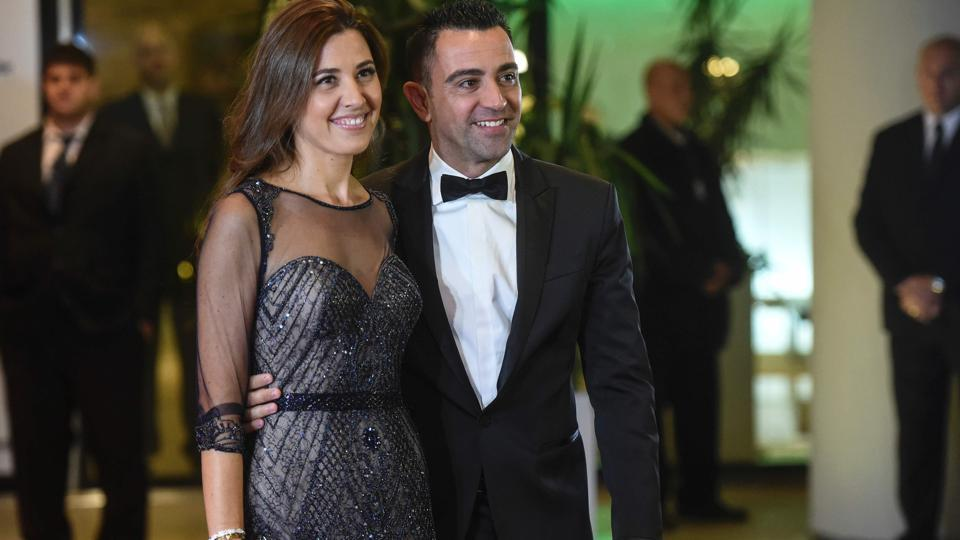 Former Barcelona's football player Xavi Hernandez and his wife pose on a red carpet upon arrival. (AFP)