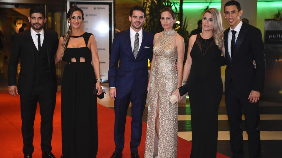 Paris Saint Germain's footballer Angel di Maria (R), Boca Juniors' footballer Fernando Gago (C) and Sevilla's footballer Ever Banegas pose with their wives. (AFP)