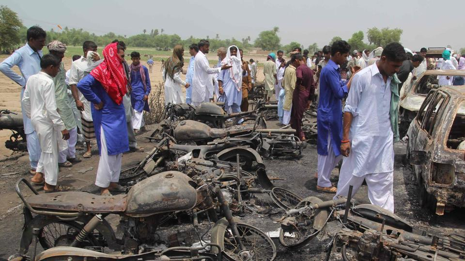 This file photo taken on June 26, 2017 shows Pakistani villagers gathering at the site of a deadly oil tanker fire following an accident in the town of Ahmedpur East. R