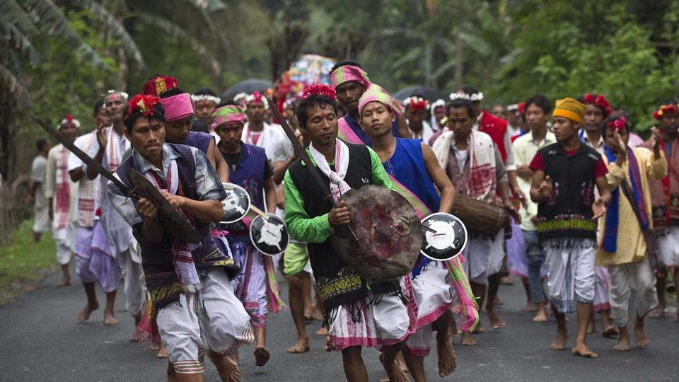 Members of  Karbi tribe in traditional attire perform a warrior dance as they take part in a religious procession during the traditional festival
