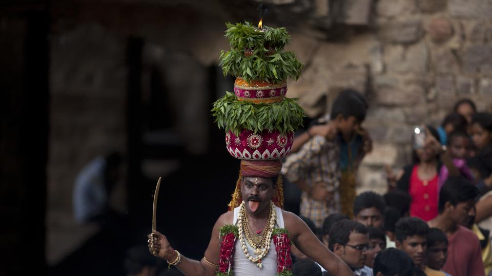 A man dances, balancing on his head a decorated pot filled with cooked rice as an offering to goddess Kali, at the Golconda Fort during the Bonalu festival in Hyderabad, Telangana. Bonalu is a month-long Hindu folk festival of the Telangana region dedicated to Kali, the Hindu goddess of destruction.  (Mahesh Kumar A. / AP)