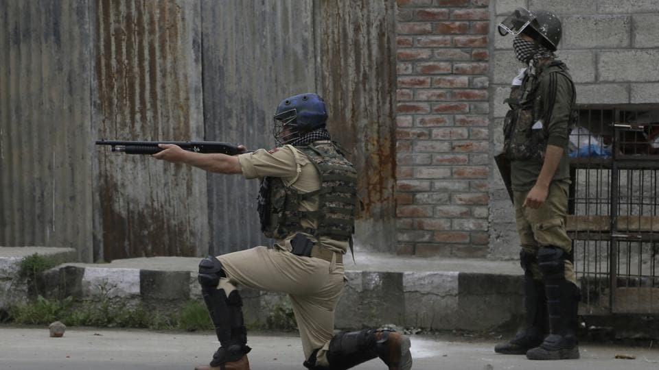 A paramilitary personnel fires a pellet gun during a protest after in Srinagar.