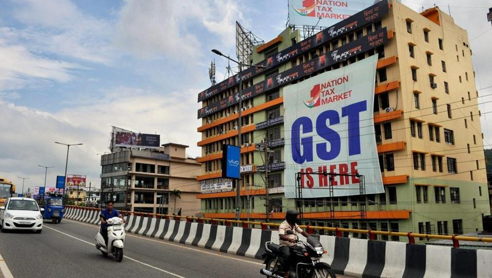 People go past a GST poster on the wall of a building, in Guwahati.