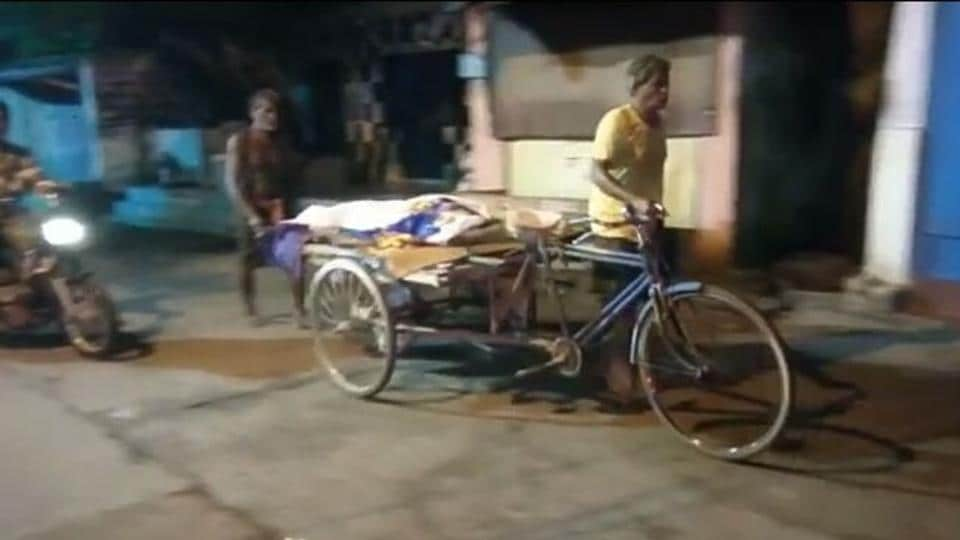Dhani Sahu carries his daughter's body on a pedal cart on Saturday night after not being able to get a hearse vehicle.