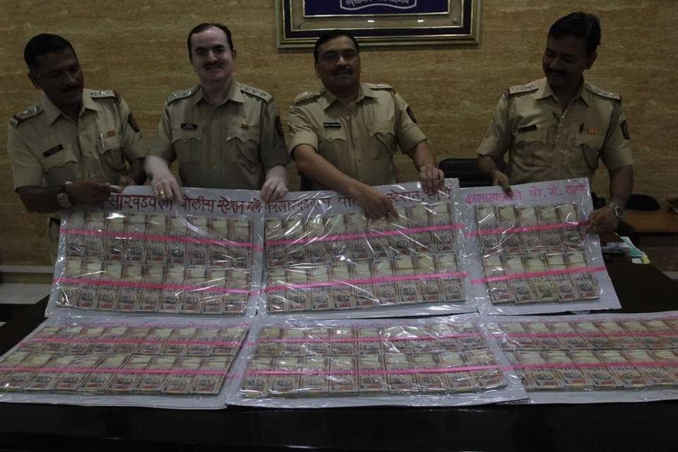 Policemen display the seized notes