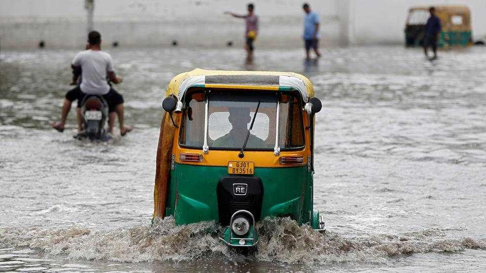 An auto-rickshaw moves through a waterlogged road after heavy rain in Ahmedabad.