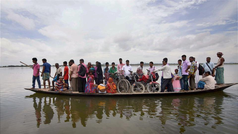 Representative Image | Villagers sit on a boat as they are transported to safety after their houses got submerged in flood waters at Balimukh village in Morigaon district of Assam.