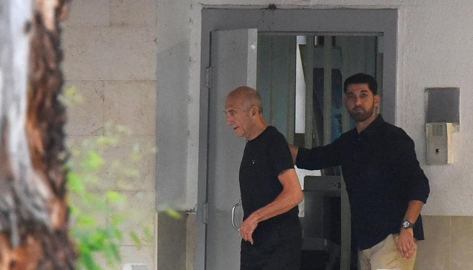 Former Israeli Prime Minister Ehud Olmert walks out of the prison door as he is released from prison after a parole board decided to cut his sentence by a third, at Maasiyahu prison near Ramle, Israel July 2, 2017.