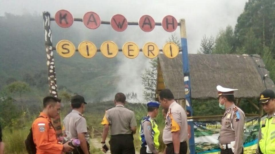 Police officers and a rescuer stand at a path leading to Sileri Crater after it erupted in Dieng, Central Java, Indonesia on July 2.