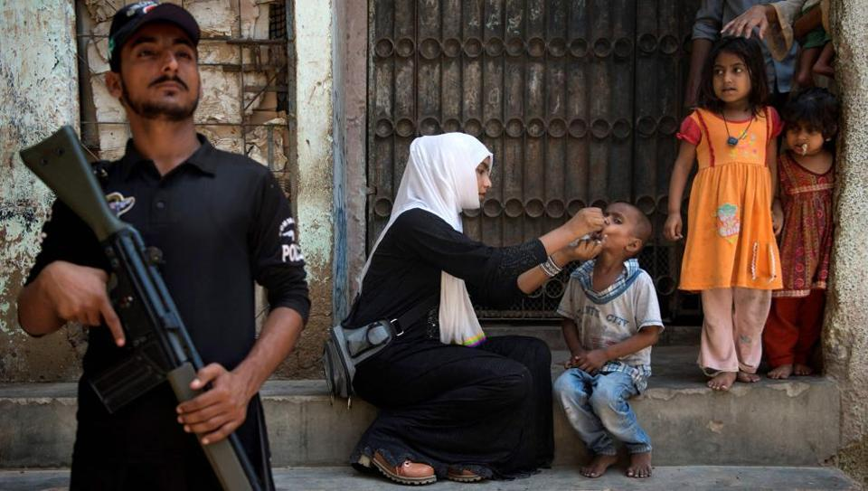 A Pakistani policeman stands guard as a health worker administers polio vaccine to a child during a vaccination campaign in Karachi in April 2017.