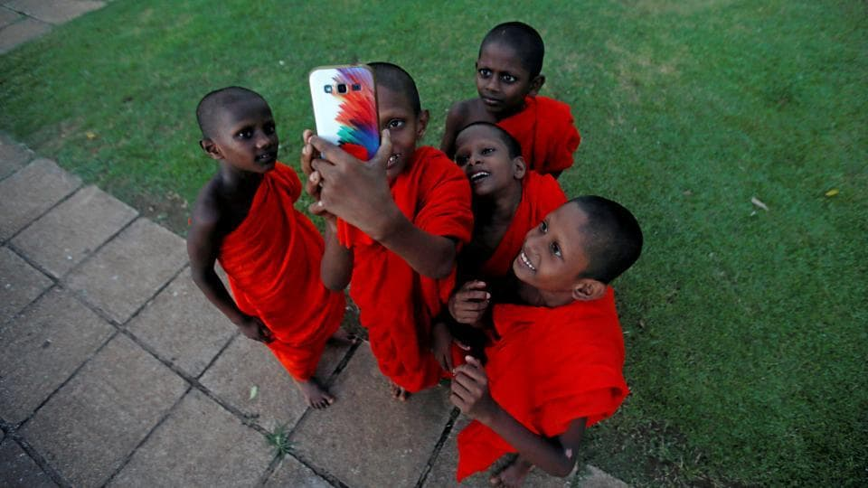 A group of novice Buddhist monks take selfies during a religious ceremony at a temple in Colombo, Sri Lanka. (Dinuka Liyanawatte / Reuters)