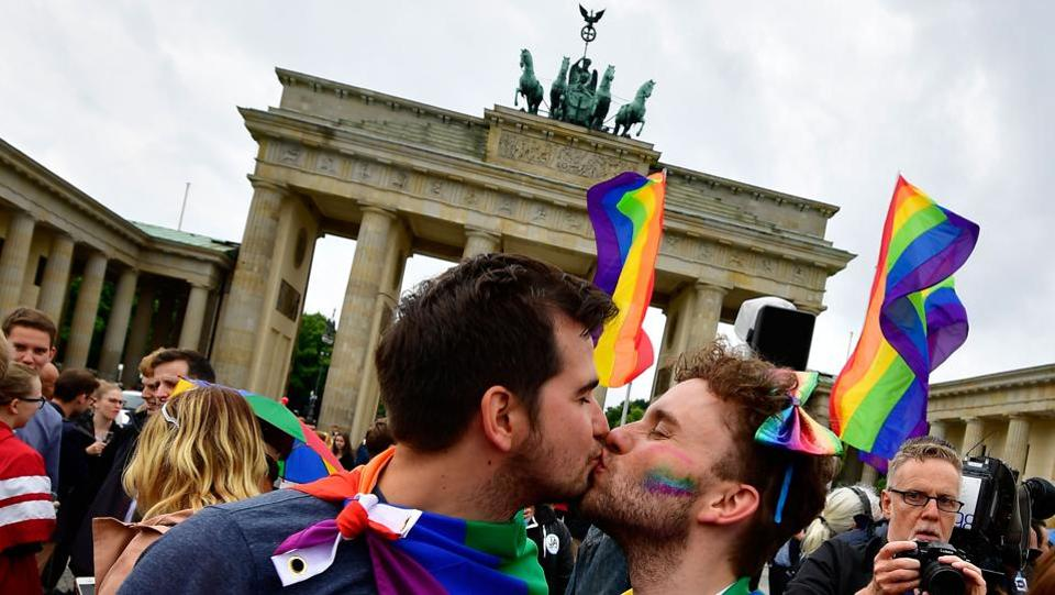 Two men kiss as they attend a rally of gays and lesbians in front of the Brandenburg Gate in Berlin, Germany. The German parliament legalised same-sex marriage, days after Chancellor Angela Merkel said she would allow her conservative lawmakers to follow their conscience in the vote. (Tobias Schwarz / AFP)