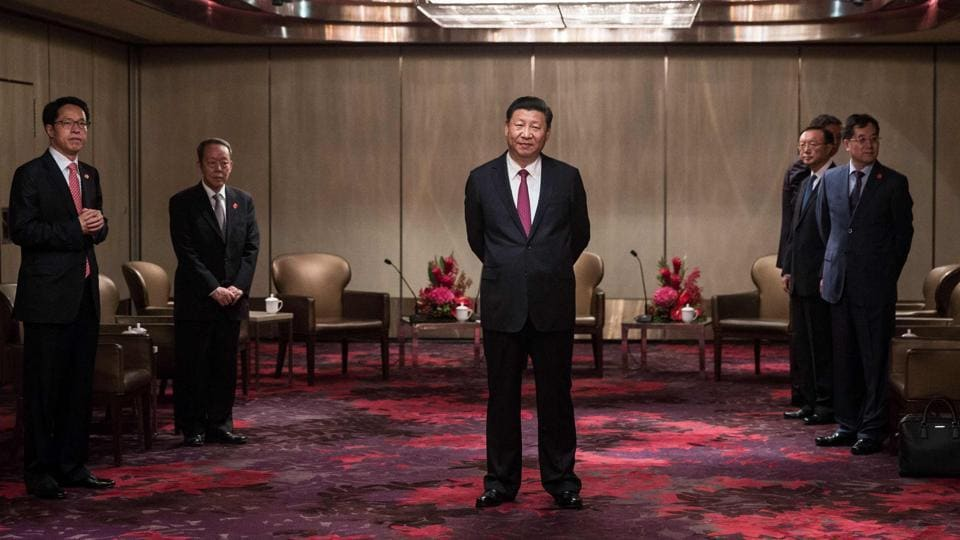 China's President Xi Jinping (C) waits to meet with Hong Kong's chief executive Leung Chun-ying at a hotel in Hong Kong as part of the 20th anniversary of the city's handover from British to Chinese rule. (Dale De La Rey / AFP)