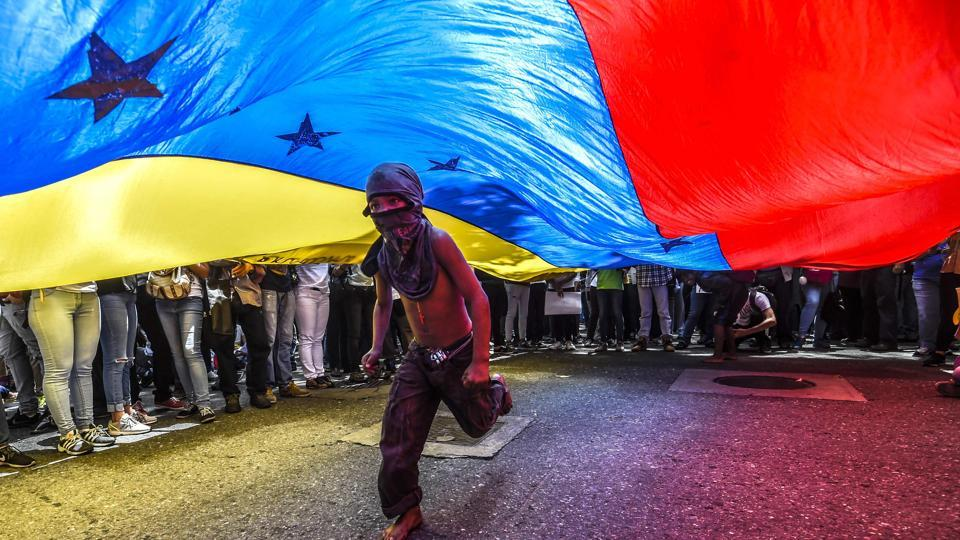 A boy runs under a Venezuelan flag during a protest of journalists and media workers against the attacks on journalists, in Caracas, Venezuela. (Juan Barreto / AFP)