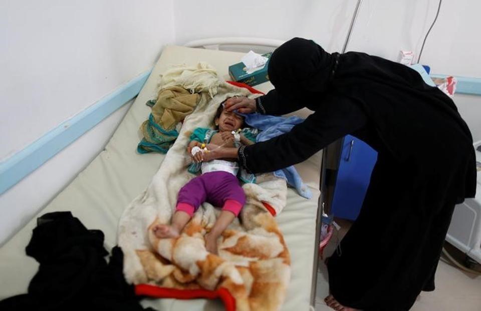 A woman helps her son as he lies on a bed at a cholera treatment center in Sanaa, Yemen June 6, 2017.