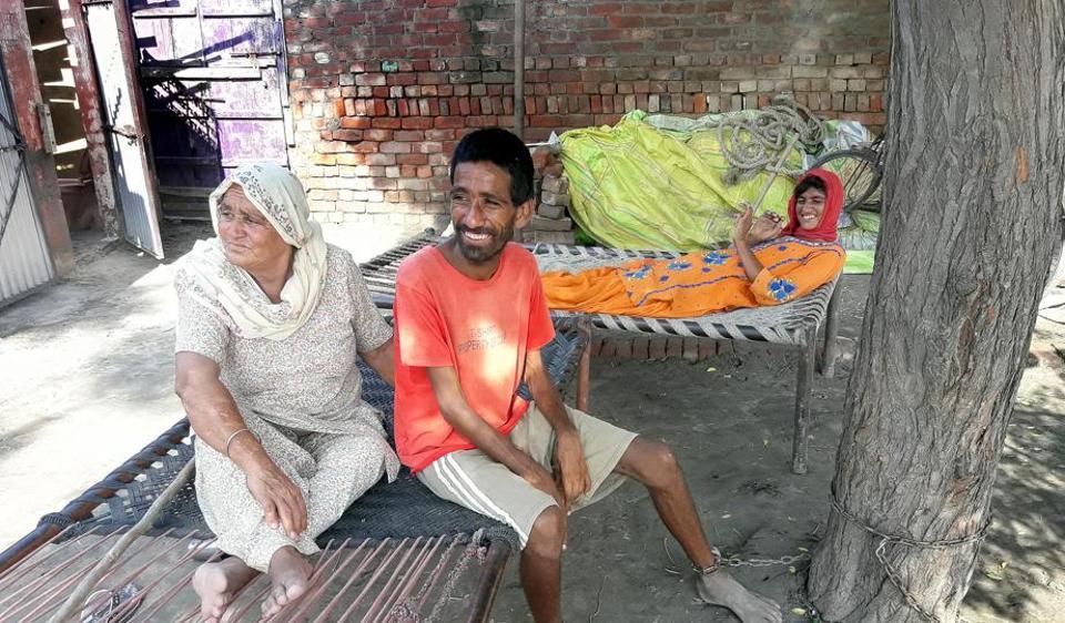 Simranjit Kaur with her chained son Gursahib Singh and daughter Kuldeep Kaur at Balehar village in Tarn Taran district on Sunday.