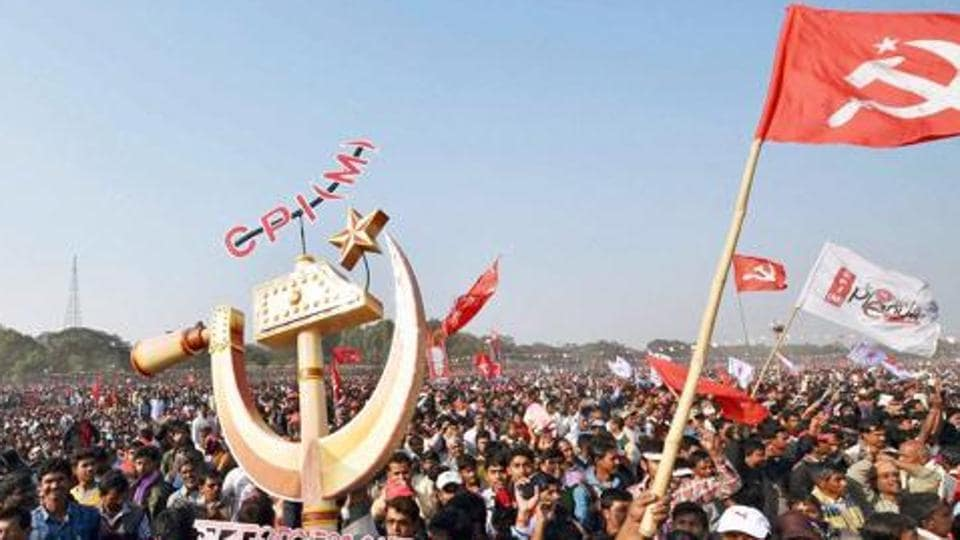 CPI(M) activists hold flags and party symbol in a rally in Kolkata