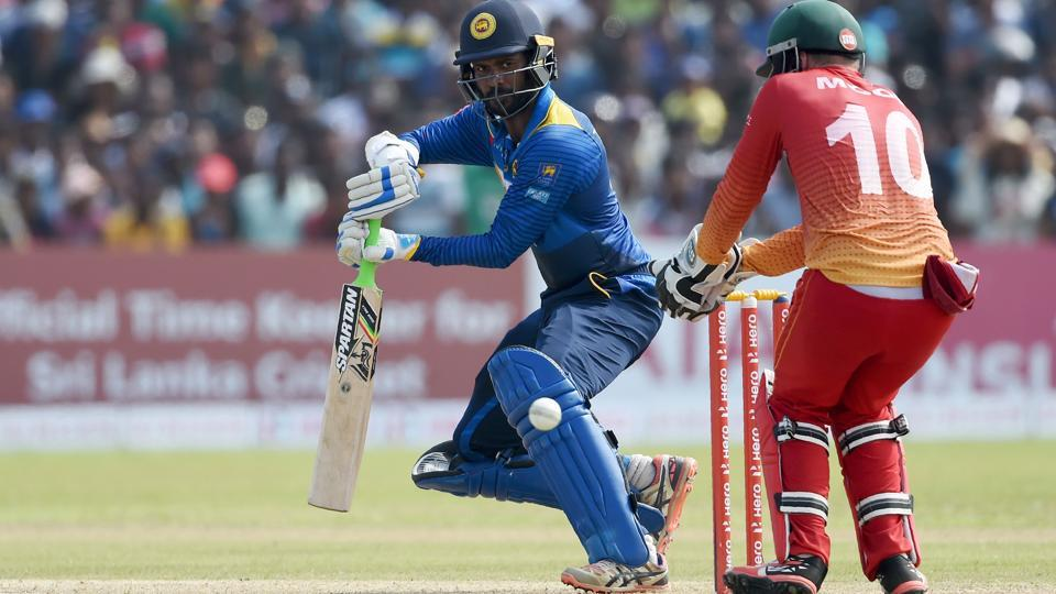 Sri Lankan cricketer Upul Tharanga (L) plays a shot as Zimbabwe wicketkeeper Peter Moor (C) looks on.