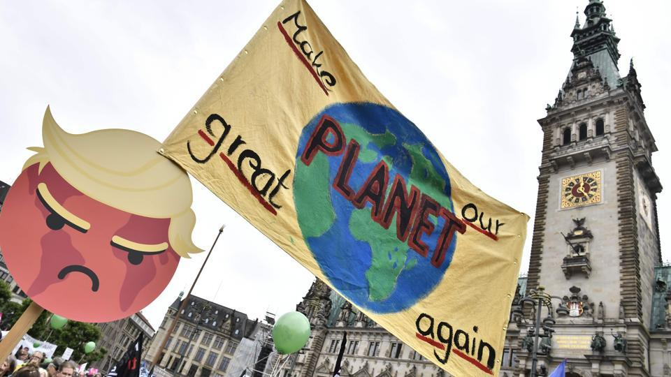 A banner is lifted in front of the Hamburg city hall (Rathaus) with a caricature of US President Trump and a play on his campaign slogan, reding 'Make our planet great again'.  (John Macdougall / AFP)