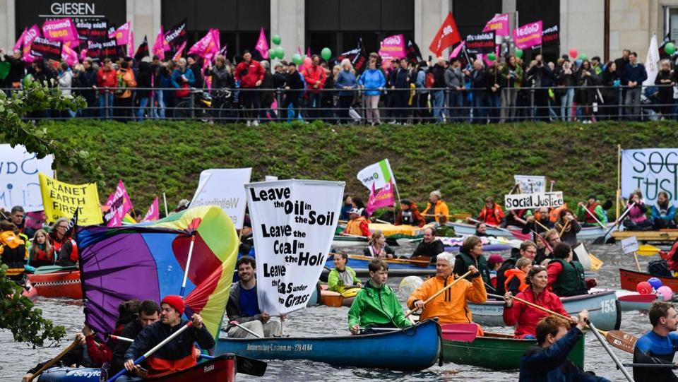 Protest boats pass demonstrators staging a simultaneous protest by the Alster river against the environmental policies of the G20 participant nations. (John Macdougall / AFP)