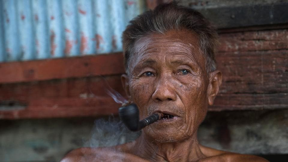 Kar Shar, a Moken leader smoking his pipe as he sits in front of his home in Makyone Galet village in the Myeik Archipelago. 'When we were young, a husband could easily support his family,' recalls Kar Shar.  (Ye Aung THU  / AFP)