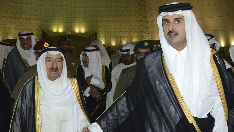 FILE- In this Wednesday, June 7, 2017 file photo released by Kuwait News Agency, KUNA, Kuwait's Emir Sheikh Sabah Al Ahmad Al Sabah, left, holds the hand of Qatar's Emir Sheikh Tamim bin Hamad Al Thani in Doha, Qatar. Qatar likely faces a deadline this weekend to comply with a list of demands issued to it by Arab nations that have cut diplomatic ties to the energy-rich country, though its leaders already have dismissed the ultimatum.