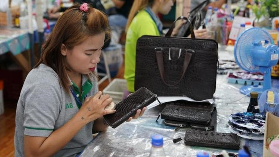 A worker polishes a wallet made from crocodile skin at Sri Ayuthaya Crocodile farm. (Athit Perawongmetha / Reuters)