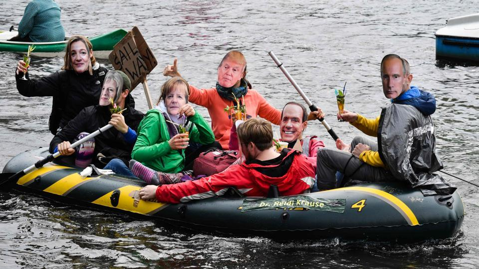 With the main protest gatherings out side the city hall, protestors wearing masks of politicians took to canoes in the Alster river drinking cocktails. (John Macdougall / AFP)