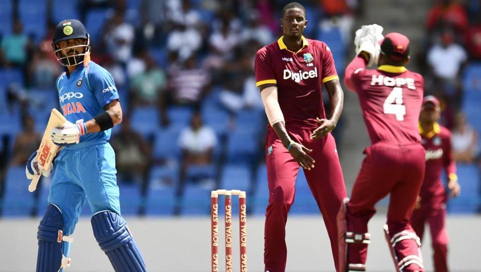 West Indies captain Jason Holder (C) celebrates the dismissal of India's Virat Kohli (L) during the fourth One Day International (ODI) match. (AFP)