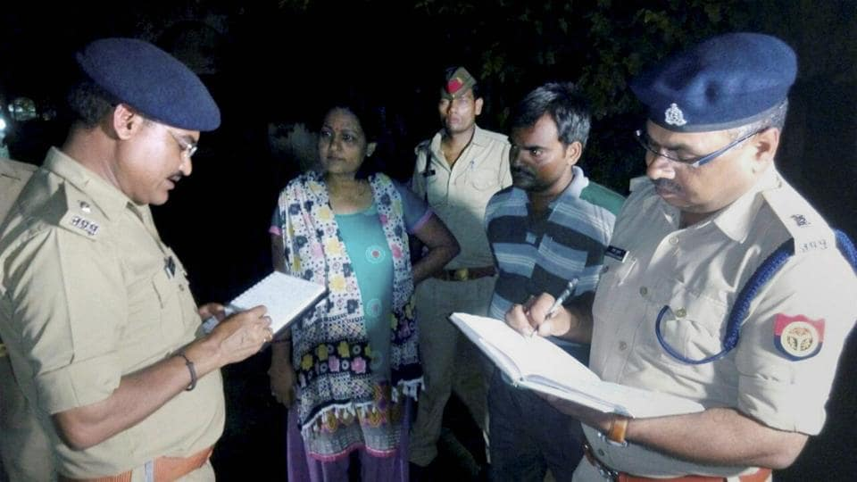 Lucknow: UP Police officers interacting with relatives of a 35-year-old woman who was attacked with acid, in Lucknow on Sunday.