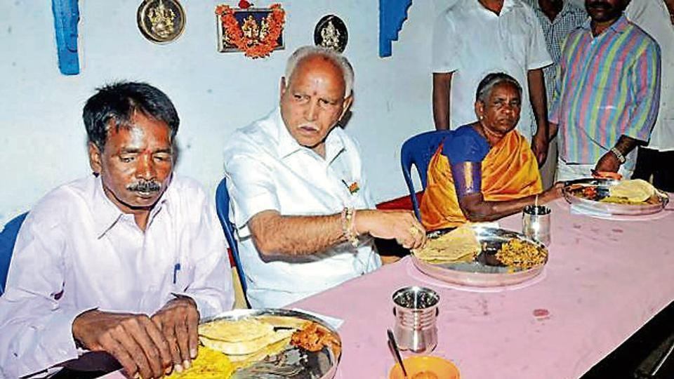 State BJP president BS Yeddyurappa has lunch with a member of the Dalit community near Chikmagalur in Karnataka.