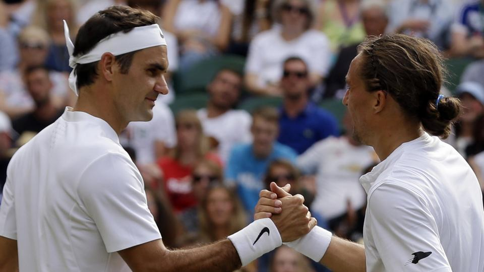 Roger Federer shakes hands with Alexandr Dolgopolov after winning their First Round match in Wimbledon.  (AP)